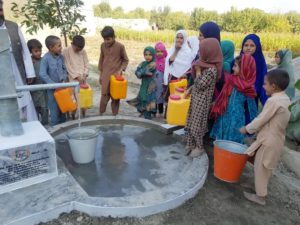 Children collect clean drinking water from a well built by Kama Relief in Afghanistan